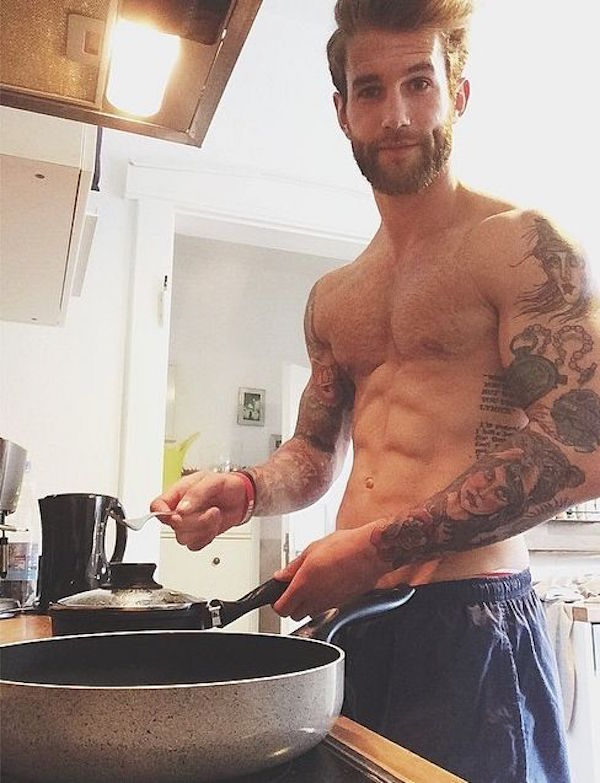 Hot, bearded, shirtless man with tattoos stands in from of a stove with for in hand while holding the handle of a small, boiling pot with a lid on it.
